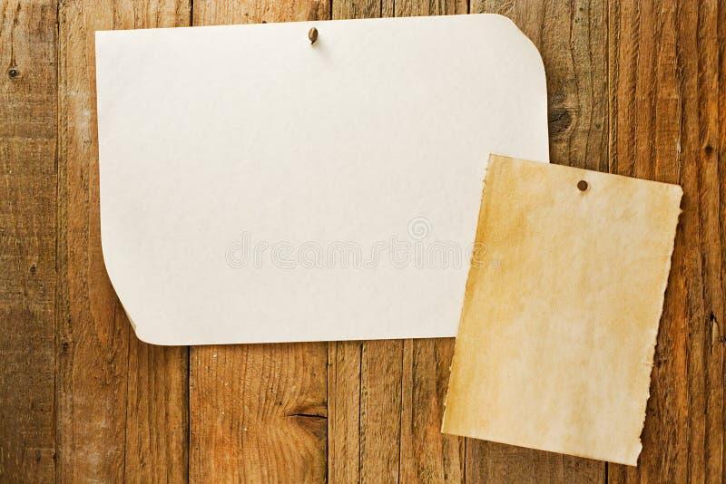 Le papier beige chiné naled au mur en bois affligé photo stock