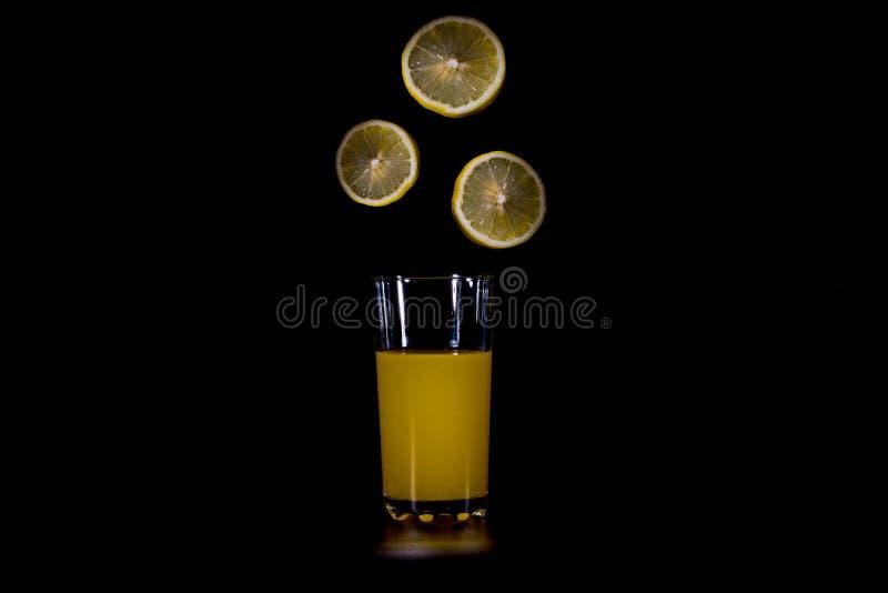 Les agrumes découpent la chute en tranches dans le verre image stock