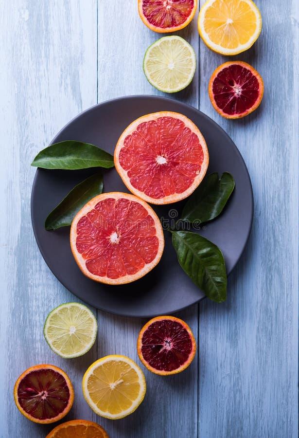 Les agrumes découpent le fond en tranches en bois de vue supérieure les pamplemousses qu'oranges de citron poussent des feuilles  images stock