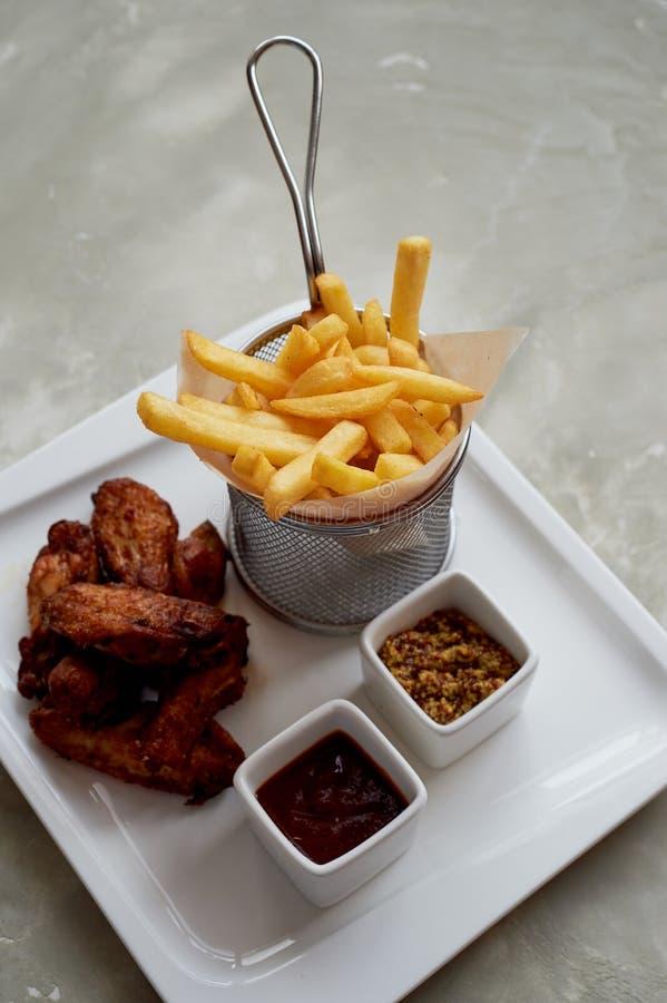 Les ailes de poulet avec le ketchup et les fritures de sauce dans un métal se tiennent sur le papier parcheminé images libres de droits