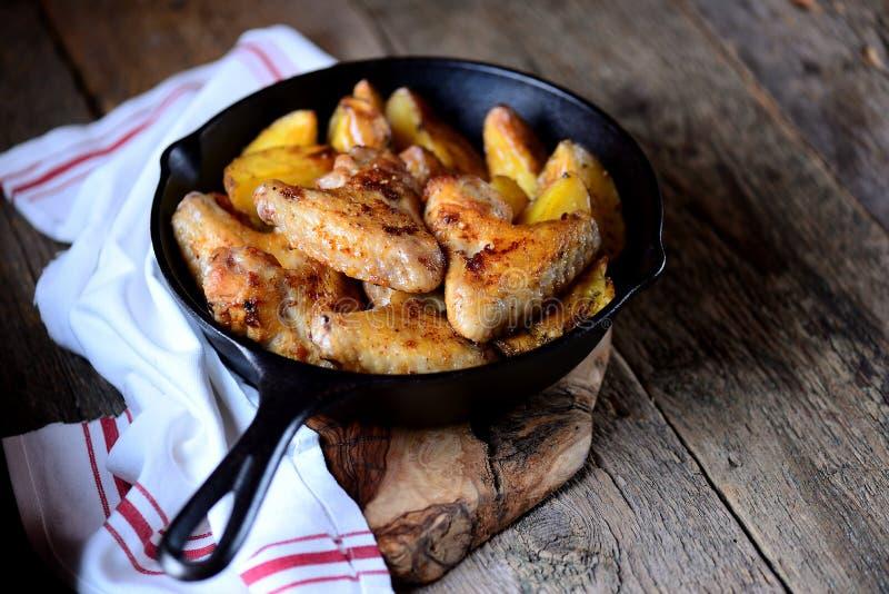 Les ailes de poulet ont fait cuire au four avec des pommes de terre en épices et herbes aromatiques - basilic, romarin, aneth et  photo stock