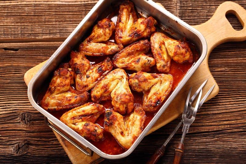 les ailes de poulet ont fait cuire au four dans une casserole sur le fond en bois photo stock. Black Bedroom Furniture Sets. Home Design Ideas