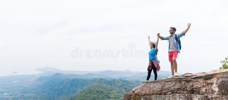 Les ajouter de touristes au sac à dos jugeant des mains augmentées sur le dessus de montagne apprécient le beau panorama de paysa photographie stock libre de droits