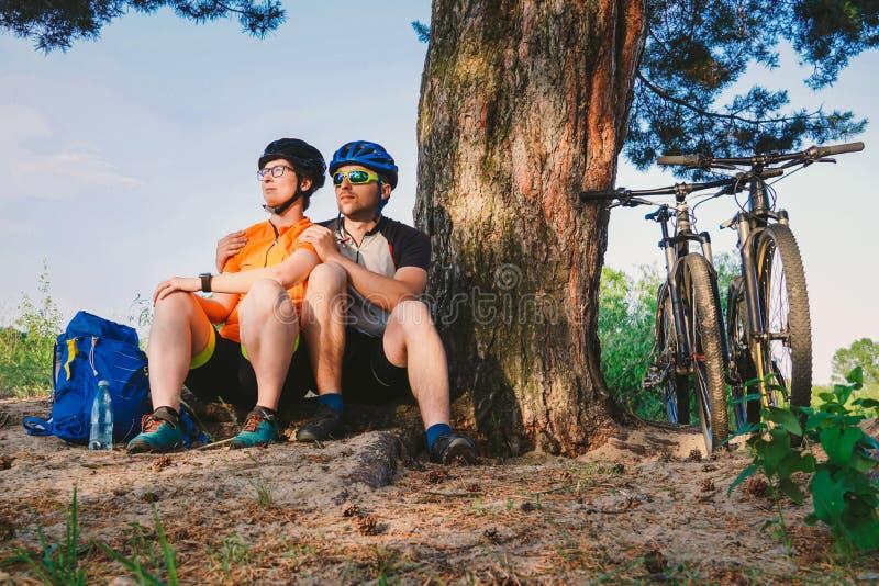 Les ajouter heureux au vélo de montagne se reposent embrassant la nature de loisirs dehors les couples heureux, mènent un mode de image libre de droits