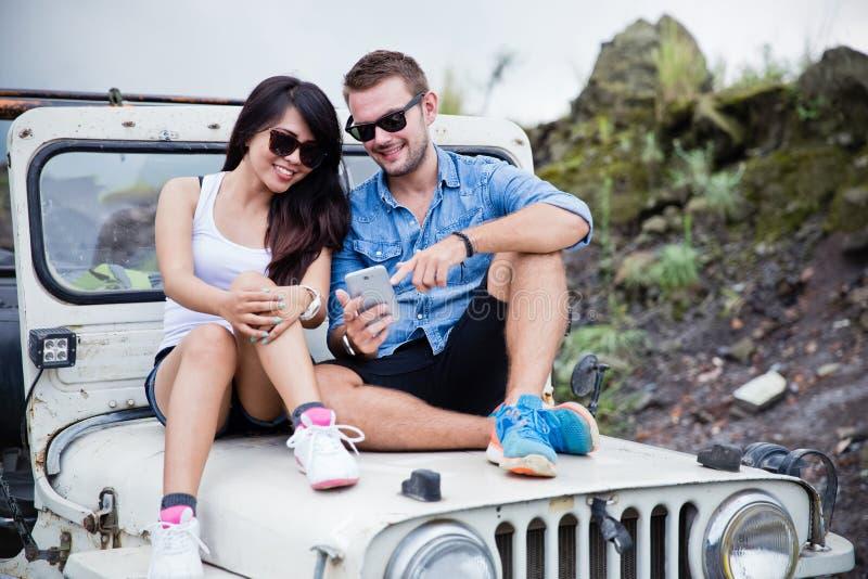 Les ajouter mélangés aux lunettes de soleil sur se reposer sur le capot d'une jeep font photo stock