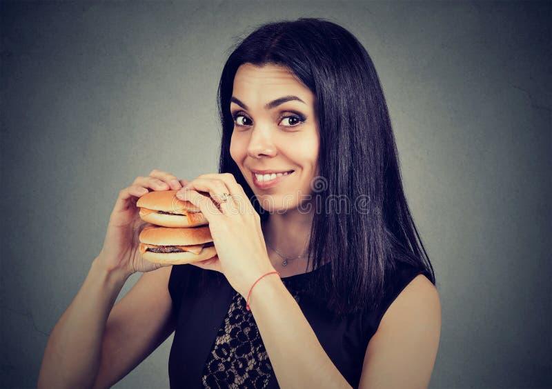 Les aliments de préparation rapide sont mon favori Femme mangeant un double cheeseburger image libre de droits