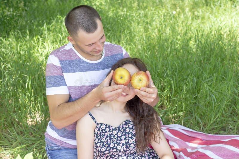 Les amants garçon et fille mouillent des pommes clôturent chaque autres des yeux ?motions Pique-nique d'?t? image libre de droits