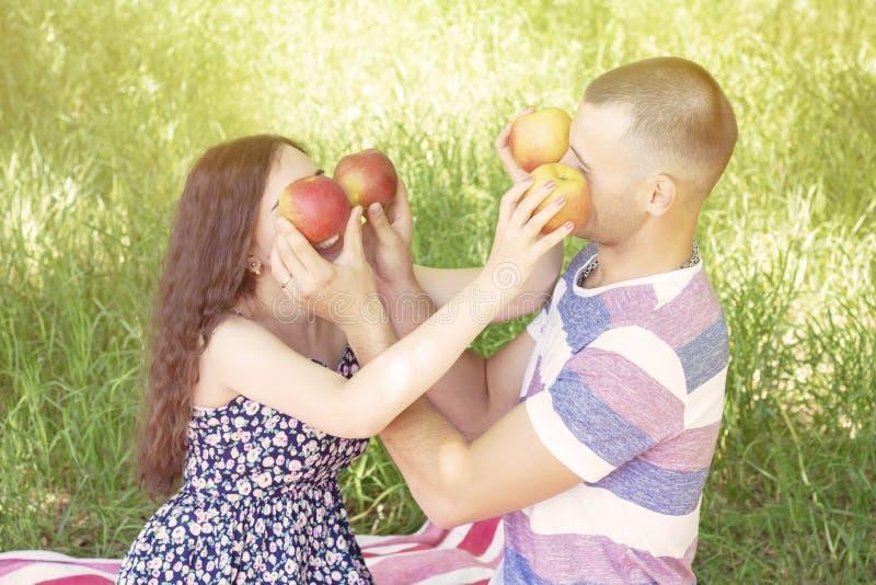 Les amants garçon et fille mouillent des pommes clôturent chaque autres des yeux ?motions Pique-nique d'?t? photos stock