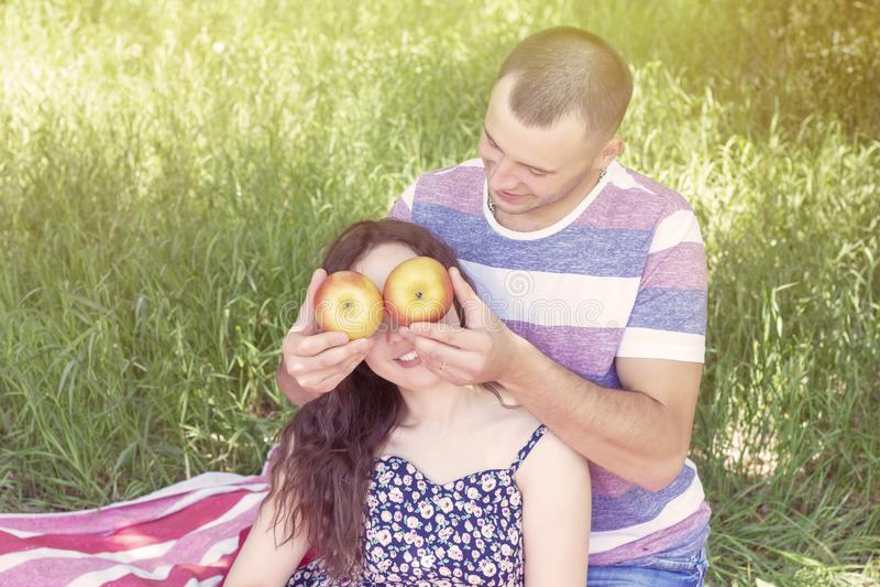 Les amants garçon et fille mouillent des pommes clôturent chaque autres des yeux ?motions Pique-nique d'?t? photographie stock libre de droits