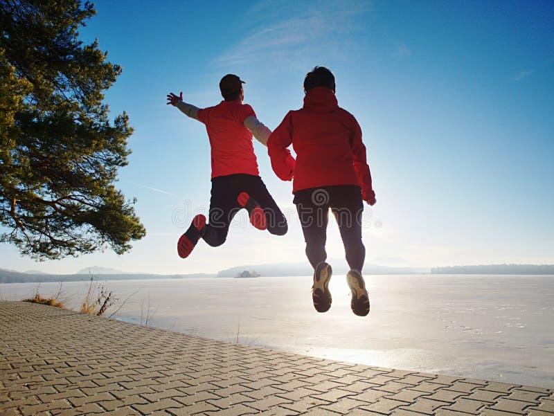 Les amants heureux de Fuuny sautent ensemble Femme et homme de pair images libres de droits