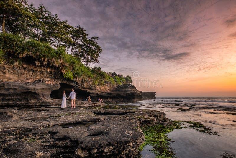 Les amants observent le troupeau des battes de la caverne sur le littoral au coucher du soleil image libre de droits