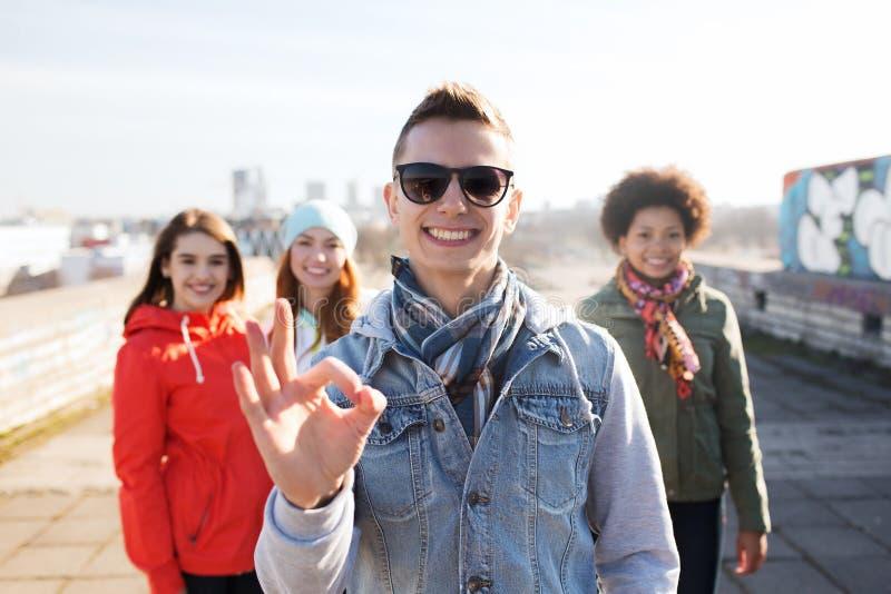 Les amis adolescents heureux montrant correct se connectent la rue photo stock