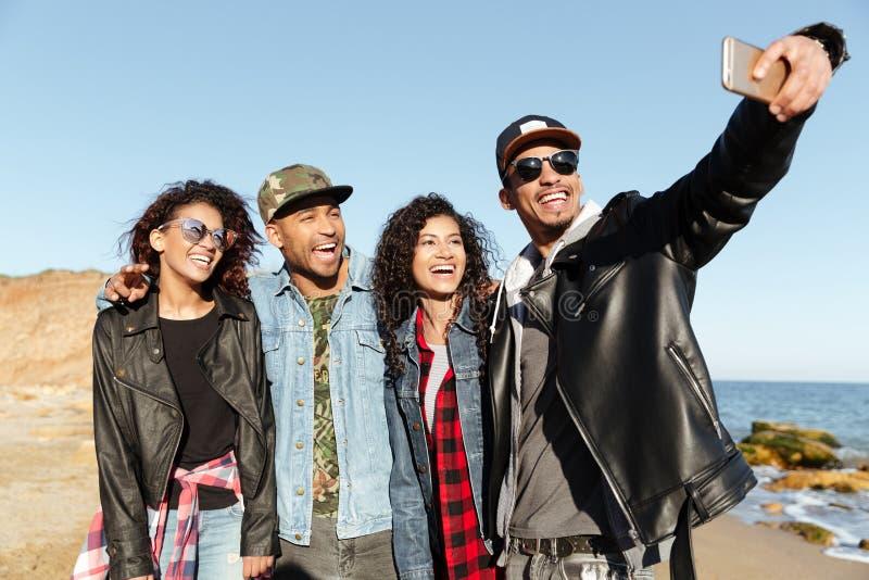 Les amis africains de sourire marchant dehors sur la plage font le selfie image libre de droits
