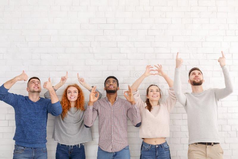 Les amis divers faisant des gestes avec remet le mur blanc image libre de droits