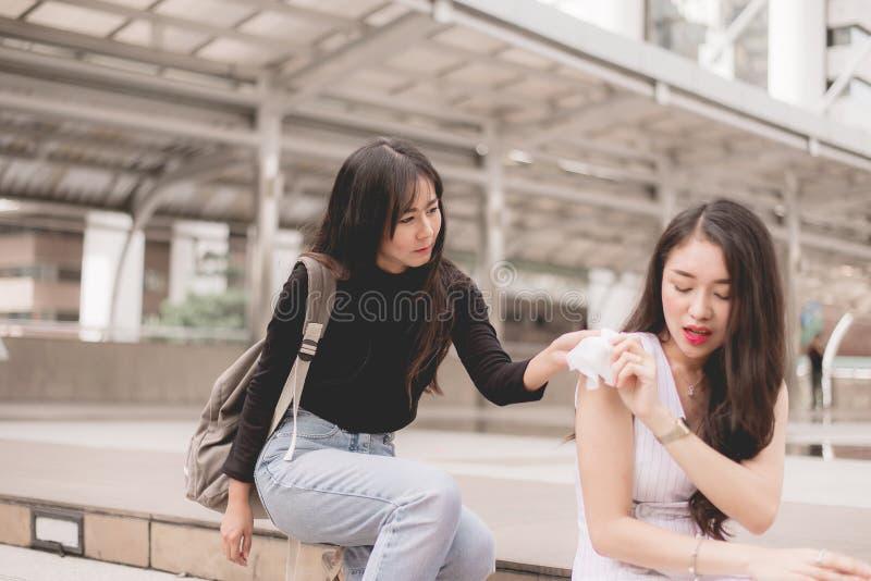 Les amis donnant le tissu à la femme asiatique déprimée, femelle malheureux soutiennent son amie photos libres de droits