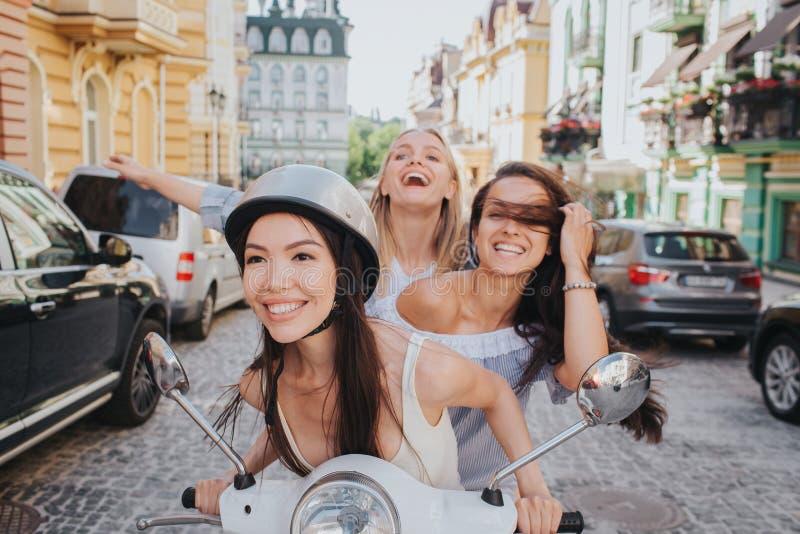 Les amis enthousiastes et magnifiques montent sur une moto La fille chinoise sourit Elle porte le casque Ses amis photos libres de droits