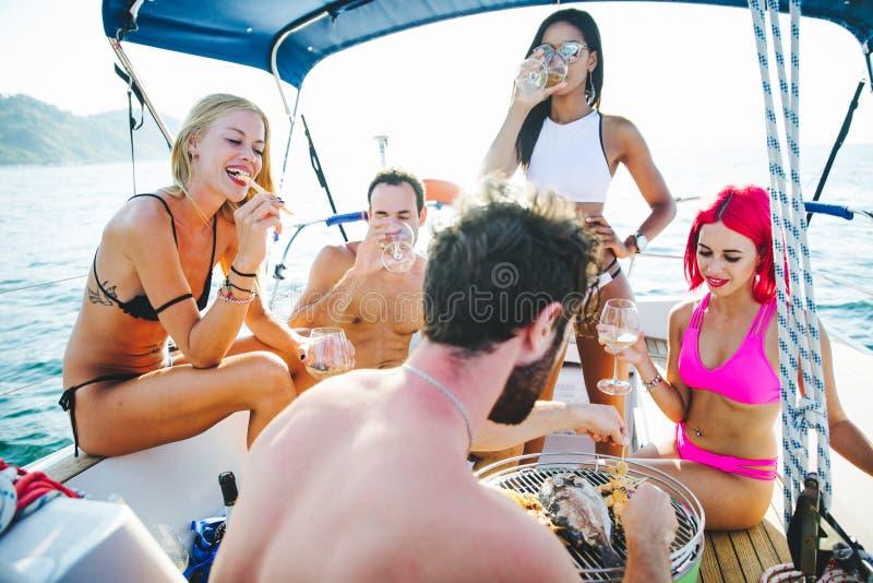 Les amis faisant des poissons grillent tout entier sur le yacht photo stock