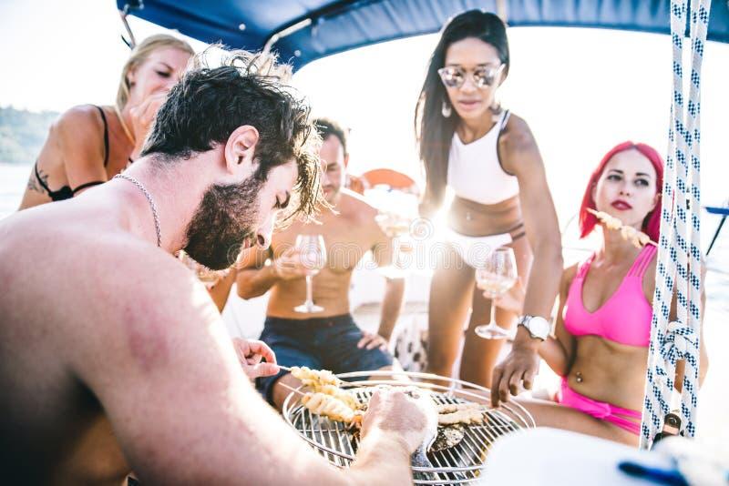 Les amis faisant des poissons grillent tout entier sur le yacht photographie stock
