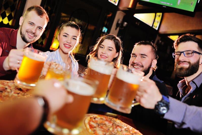 Les amis gais boivent de la bière pression et font tinter des verres dans une barre ou un bar photographie stock libre de droits