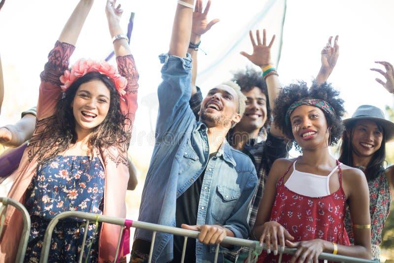 Les amis heureux avec des bras ont soulevé apprécier pendant le festival de musique photos libres de droits