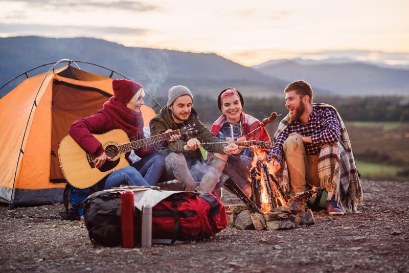 Les amis heureux ayant un pique-nique aux montagnes, ils des boissons d'?nergie causent, de boissons, jouant sur la guitare et fo images libres de droits