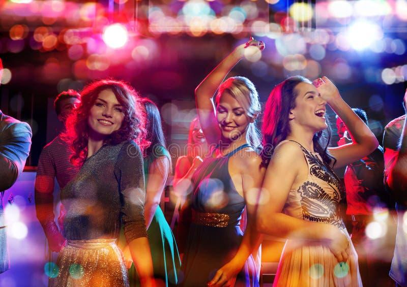 Les amis heureux dansant dans le club avec des vacances s'allume images stock