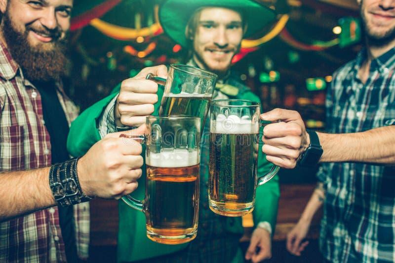 Les amis heureux gais se tiennent ensemble dans le bar et l'acclamation Ils tiennent des tasses de bière près de l'un l'autre Sou image libre de droits