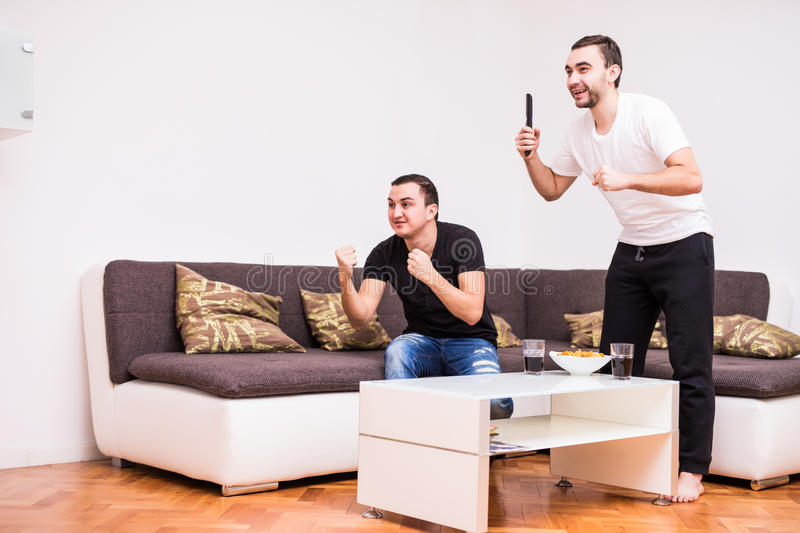 Les amis observant le match de football à la TV à la maison avec la victoire crie photo stock
