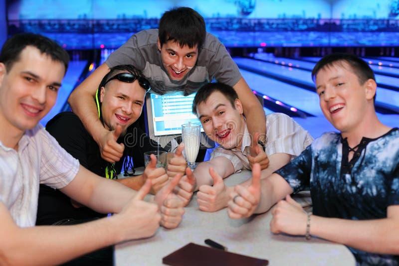 Les amis s'asseyent à la table et au pouce vers le haut dans le bowling photographie stock libre de droits