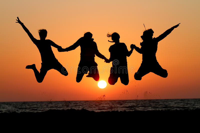 Les amis sautant dans le coucher du soleil à la plage image libre de droits