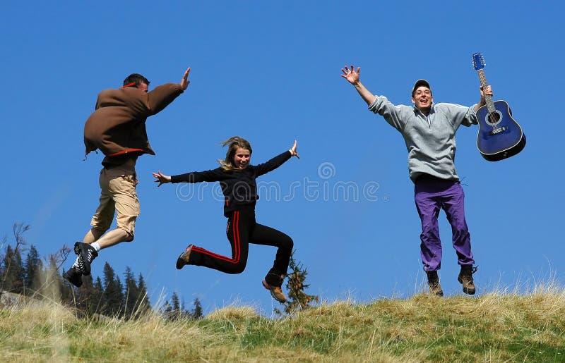 Les amis saute par-dessus une zone d'herbe sur la montagne photo libre de droits