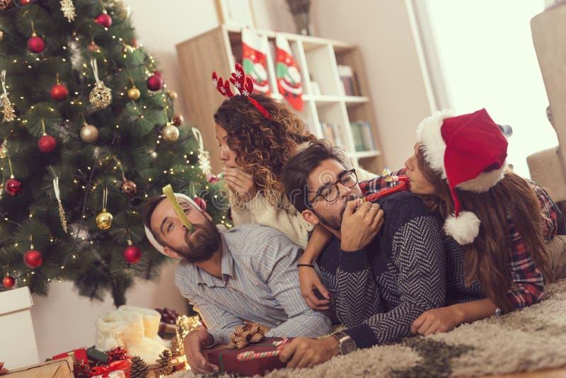 Les amis soufflant la partie siffle le jour de Noël images stock