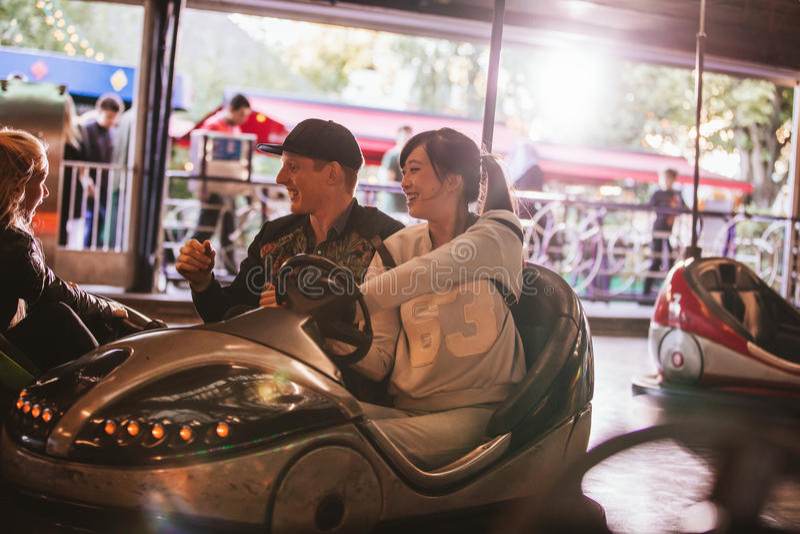 Les amis sur la voiture de butoir montent en parc d'attractions photo stock