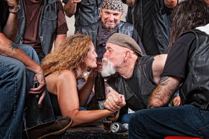 Les amoureux embrassent tandis que lutte de bras photographie stock libre de droits