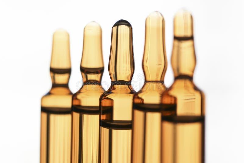 Les ampoules du verre avec le vaccin ont photographié dans la lumière blanche image libre de droits