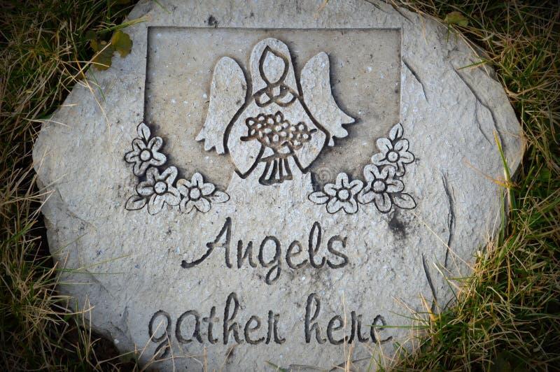 Les anges recueillent ici la pierre photos stock