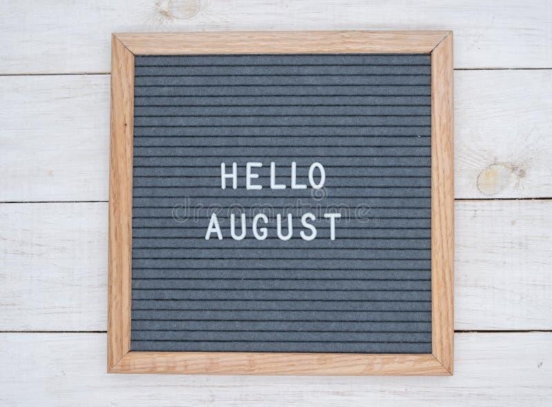 Les anglais textotent bonjour août sur un panneau de lettre dans les lettres blanches sur un fond gris images stock