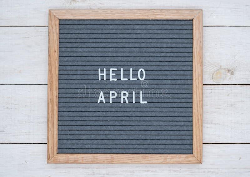 Les anglais textotent bonjour avril sur un panneau de lettre dans les lettres blanches sur un fond gris photographie stock libre de droits