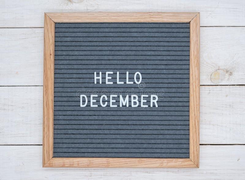 Les anglais textotent bonjour décembre sur un panneau de lettre dans les lettres blanches sur un fond gris photos stock