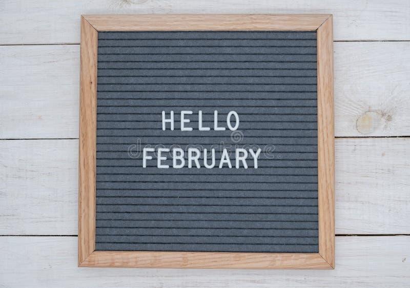 Les anglais textotent bonjour février sur un panneau de lettre dans les lettres blanches sur un fond gris photographie stock libre de droits