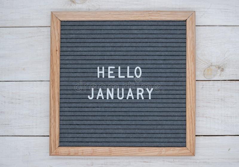 Les anglais textotent bonjour janvier sur un panneau de lettre dans les lettres blanches sur un fond gris photos libres de droits