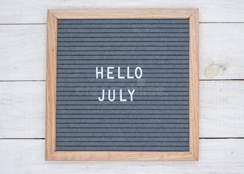Les anglais textotent bonjour juillet sur un panneau de lettre dans les lettres blanches sur un fond gris images stock