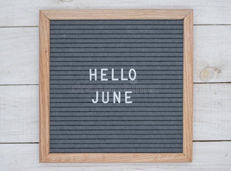 Les anglais textotent bonjour juin sur un panneau de lettre dans les lettres blanches sur un fond gris photographie stock