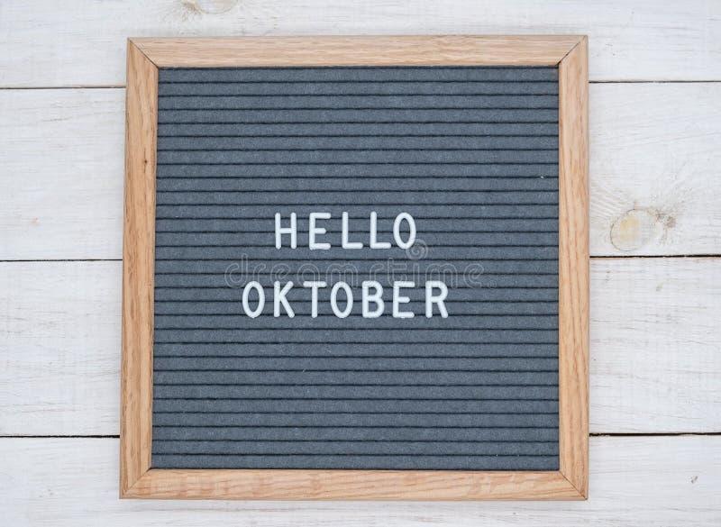 Les anglais textotent bonjour octobre sur un panneau de lettre dans les lettres blanches sur un fond gris photographie stock