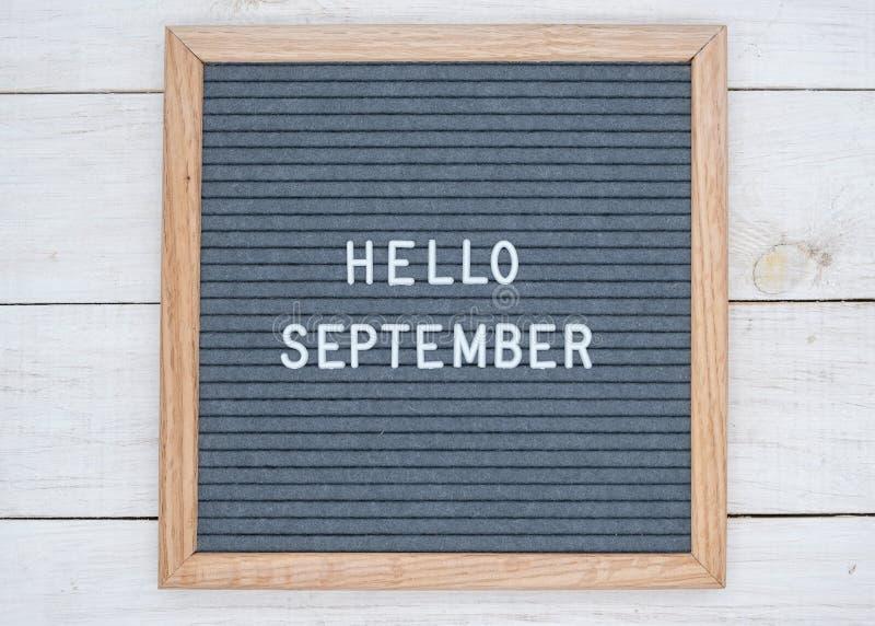 Les anglais textotent bonjour septembre sur un panneau de lettre dans les lettres blanches sur un fond gris photographie stock