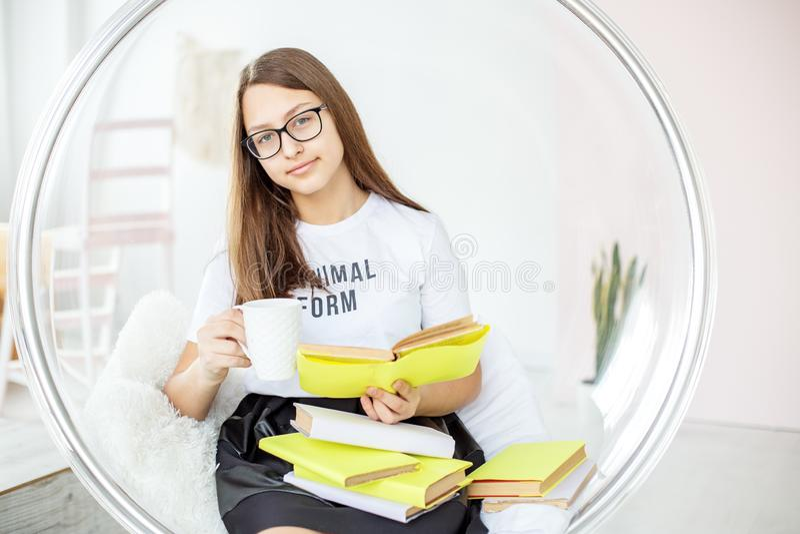 Les années de l'adolescence lisent un livre avec des verres Thé potable Concept d'éducation, passe-temps et étude et jour de livr photo stock