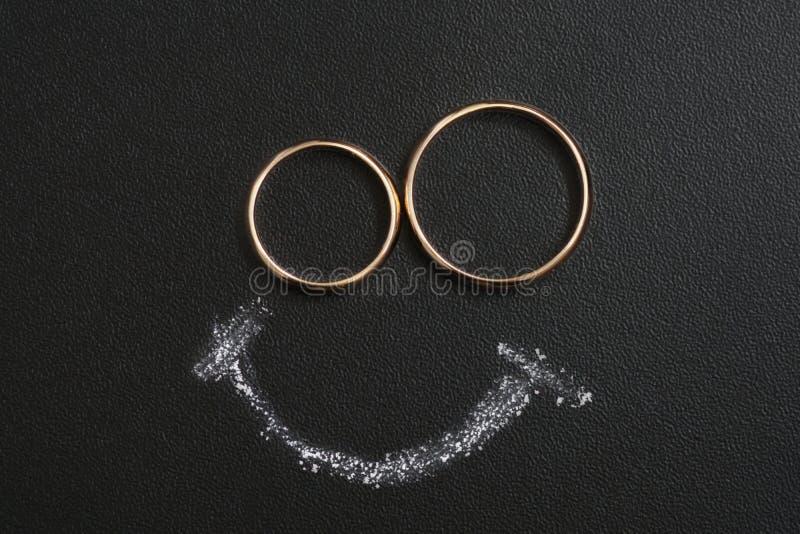 Les anneaux les épousant et le dessin de sourire avec calfatent sur le calkboard photographie stock
