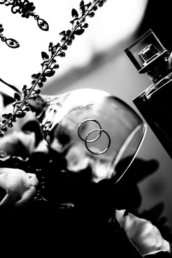 Les anneaux de mariage des jeunes mari?s sont dans le verre photographie stock libre de droits