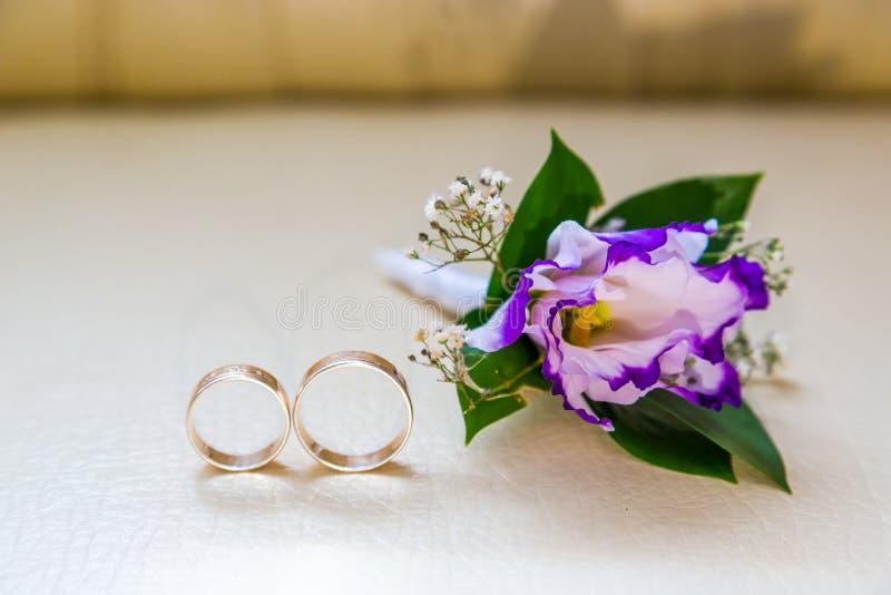 Les anneaux de mariage se trouvent à côté de la bouteille de mariage de fleurs pourpres image libre de droits