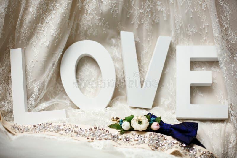 Les anneaux de mariage se trouvent devant l'amour de mot photographie stock